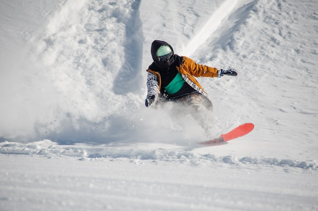 Young snowboarder in colorful sportswear riding with snowboard down powder snow hill Premium Photo