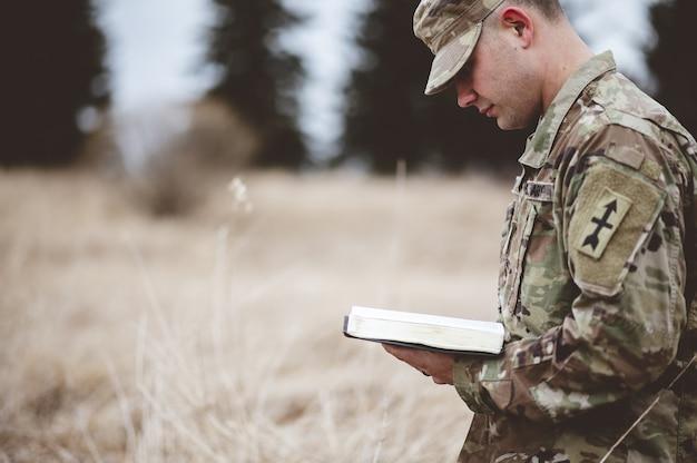 フィールドで聖書を読んでいる若い兵士 無料写真