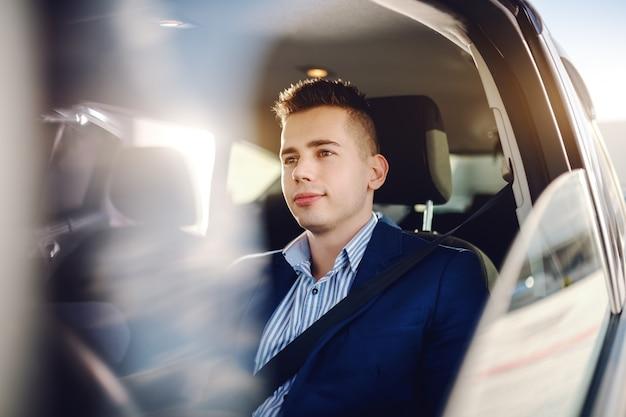 Молодой сложный человек кавказской одет смарт-случайные вождения автомобиля и глядя на шоссе. Premium Фотографии