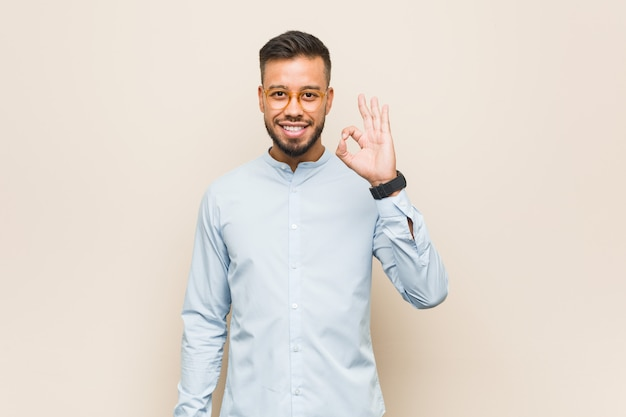 Young south-asian business man cheerful and confident showing ok gesture. Premium Photo