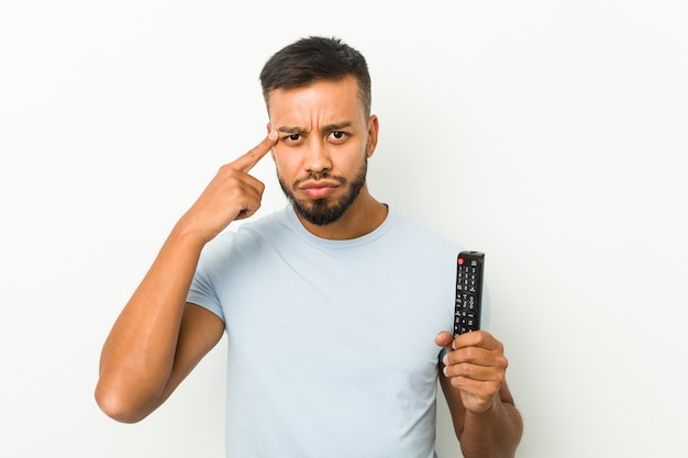 man pointing to his head and with a doubt expression while handing a remote control
