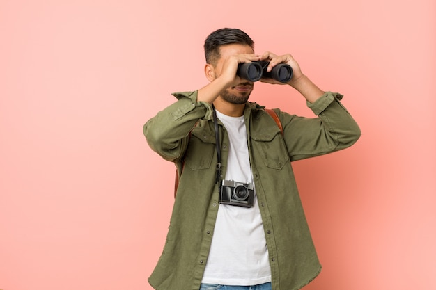 Young south asian man looking through a binoculars. Premium Photo
