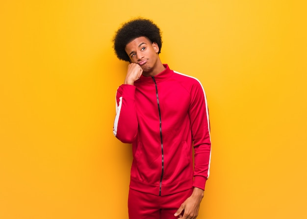 Young sport black man over an orange wall thinking of something, looking to the side Premium Photo