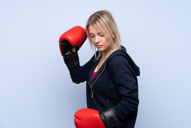 Young sport blonde woman over isolated blue wall with boxing gloves Premium Photo