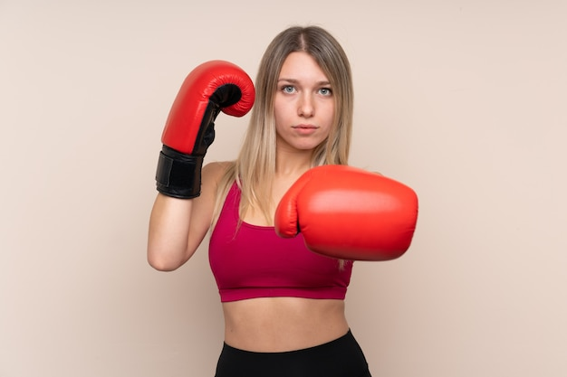Young sport blonde woman over isolated wall with boxing gloves Premium Photo