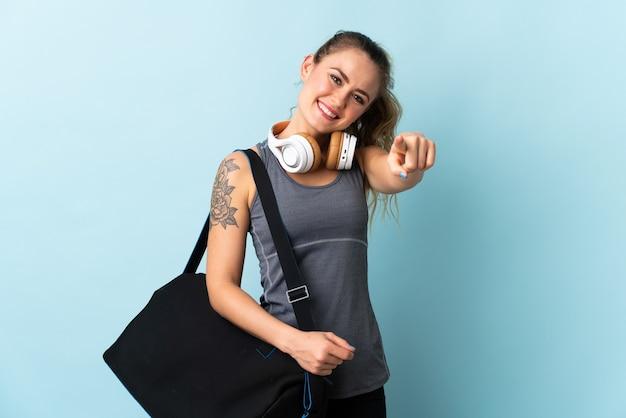幸せな表情で青いポインティングフロントに分離されたスポーツバッグを持つ若いスポーツブラジルの女性 Premium写真