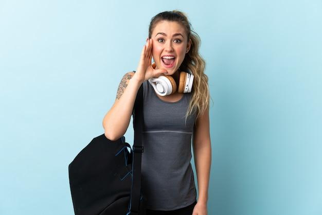口を大きく開いて青い叫びに分離されたスポーツバッグを持つ若いスポーツブラジルの女性 Premium写真