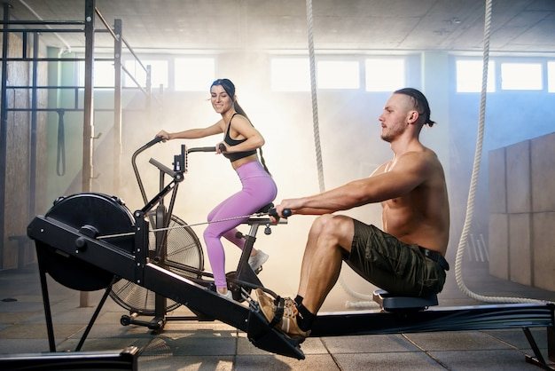 Young sport couple doing exercises on the simulators in the gym. Premium Photo