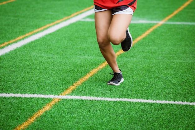 Young sport girl running on sport field Premium Photo