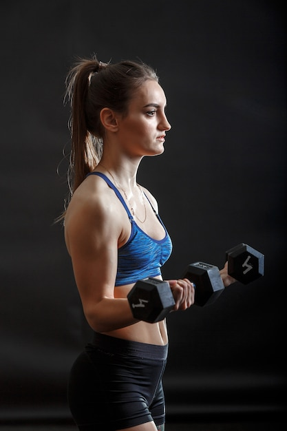 A young sport lady with ponytail hairstyle in fitness clothes training with dumbells Premium Photo