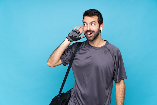 Young sport man with beard over isolated blue  listening to something by putting hand on the ear Premium Photo