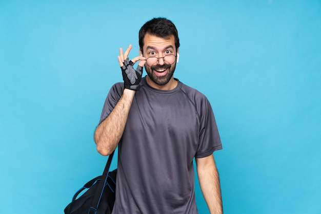 Young sport man with beard over isolated blue  with glasses and surprised Premium Photo