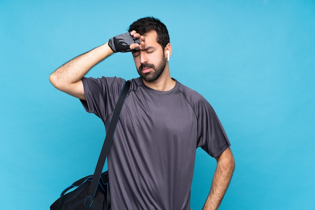 Young sport man with beard over isolated blue  with tired and sick expression Premium Photo