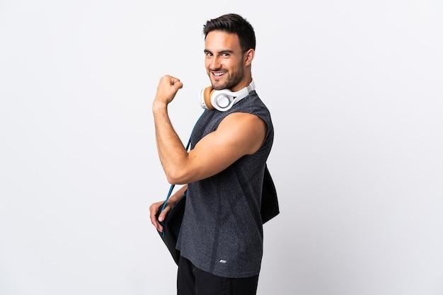 強いジェスチャーをしている白い背景で隔離のスポーツバッグを持つ若いスポーツ男 Premium写真
