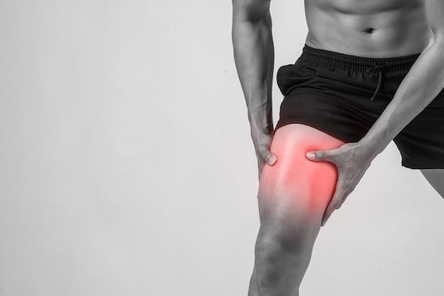 흰색에 고립 된 인대 부상을 겪고 고통에 그의 손으로 무릎을 잡고 강한 운동 다리와 젊은 스포츠 남자. 무료 사진