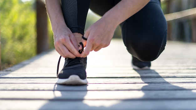 Young sport woman doing exercise in the park tying the laces Premium Photo