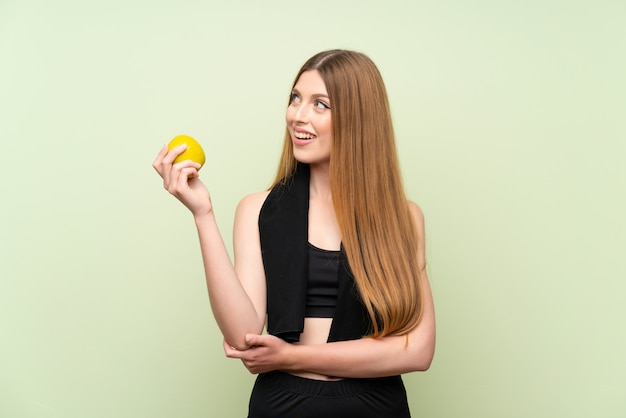 Young sport woman  on green  with an apple Premium Photo