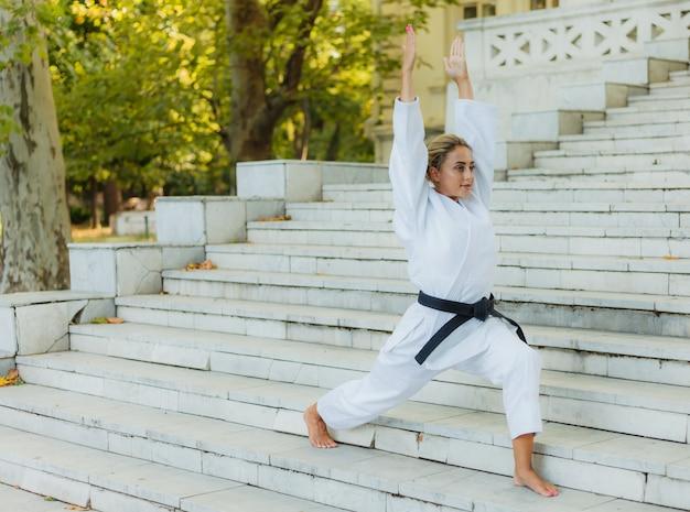 Молодая спортивная женщина в белом кимоно с черным поясом делает разминку на лестнице перед тренировкой. боевые искусства, самооборона Premium Фотографии