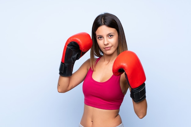 Young sport woman over isolated blue  with boxing gloves Premium Photo