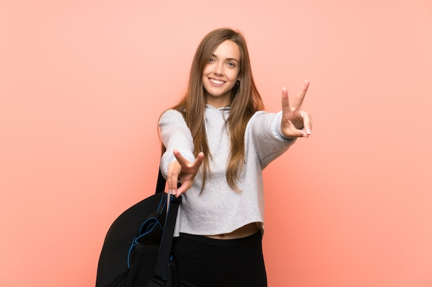 Young sport woman isolated pink  smiling and showing victory sign Premium Photo