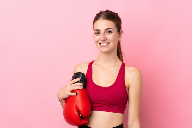 Young sport woman over isolated pink wall with boxing gloves Premium Photo