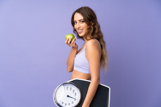 Young sport woman over isolated purple wall with weighing machine and with an apple Premium Photo