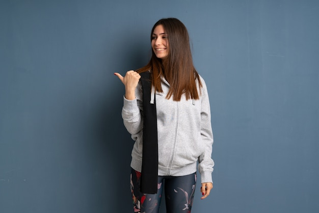 Young sport woman pointing to the side to present a product Premium Photo