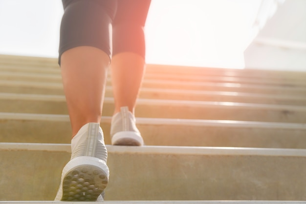 Young sport woman running up on stone stairs with sun spot background. workout and diet concept. Premium Photo
