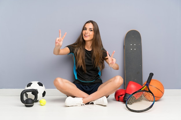 Young sport woman sitting on the floor smiling and showing victory sign Premium Photo