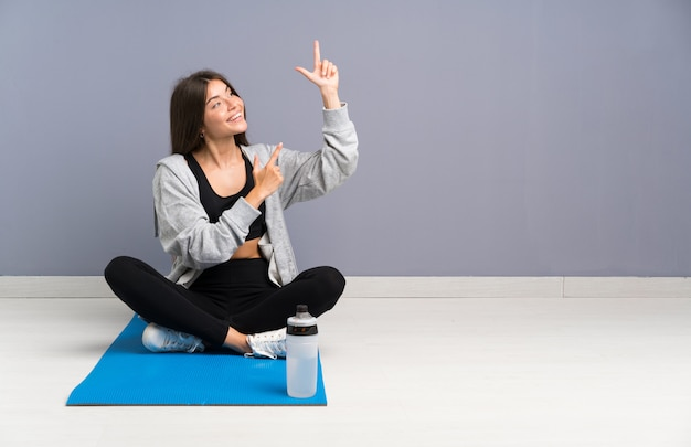 Young sport woman sitting on the floor with mat pointing with the index finger a great idea Premium Photo