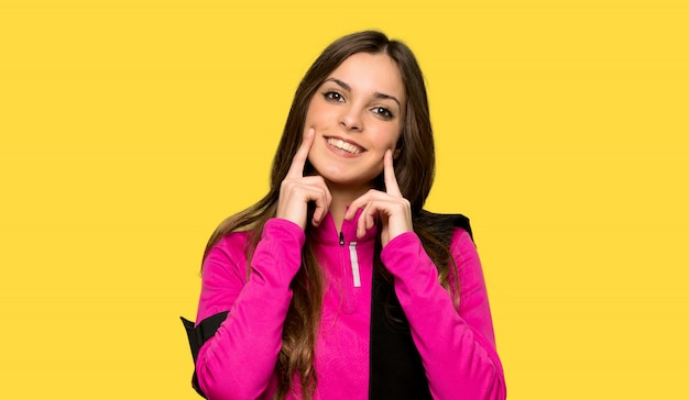 Young sport woman smiling with a happy and pleasant expression over isolated yellow background Premium Photo