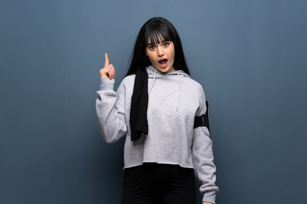 Young sport woman thinking an idea pointing the finger up Premium Photo