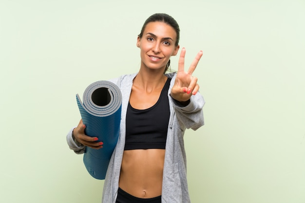 Young sport woman with mat over isolated green wall smiling and showing victory sign Premium Photo