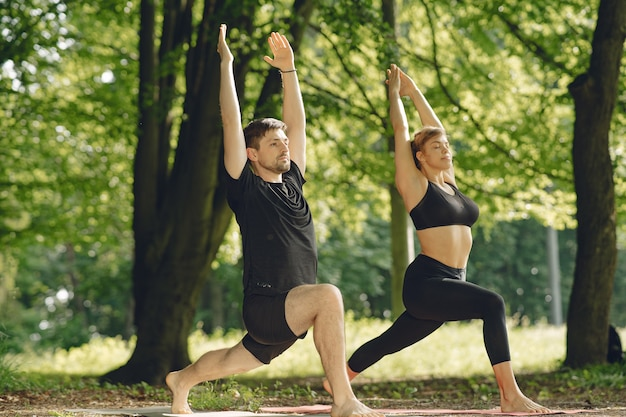 Young sportive couple doing yoga fitness . people in a summer park. Free Photo