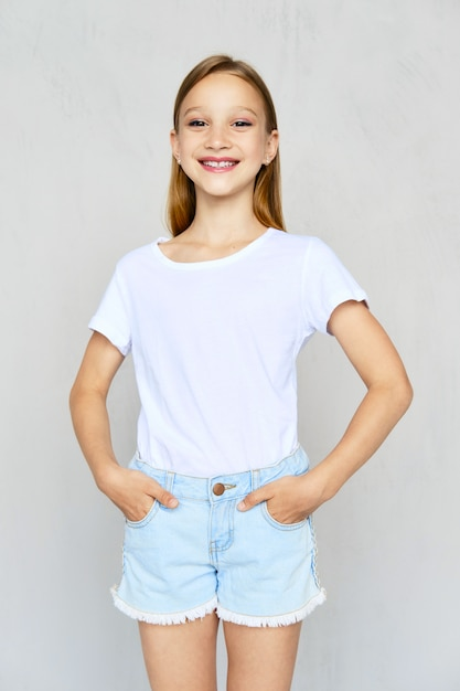 Young sportive girl in t-shirt and jeans shorts posing in studio Premium Photo