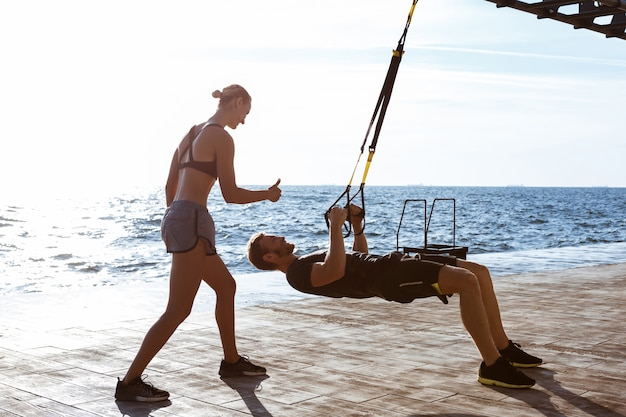 Young sportive people training with trx near sea in the morning. Free Photo