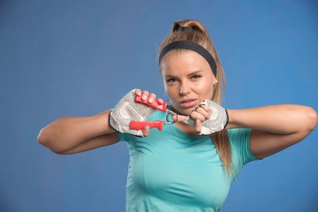 Молодая спортивная женщина, держащая руку, протягивающую резину и выглядит усталой. Бесплатные Фотографии