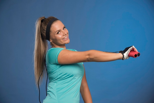 Young sportive woman holding jumping ropes and stretching her shoulder. Free Photo