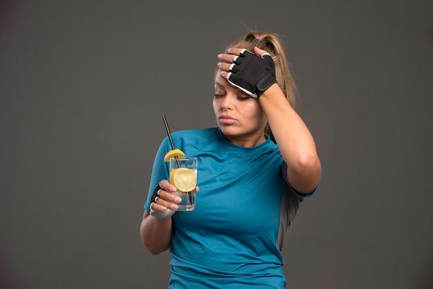Молодая спортивная женщина устала и пьет воду с лимоном. Бесплатные Фотографии