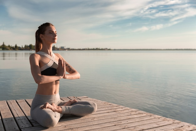Young sports lady at the beach make meditation exercises. Free Photo