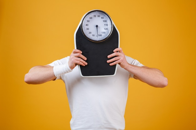 Young sports man hiding face behind weight scales Free Photo