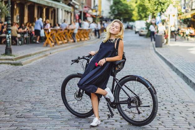 Young sports woman on a bicycle in a european city. sports in urban environments. Free Photo