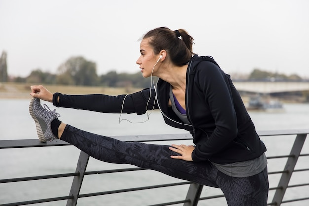 Young sports woman stretching legs Premium Photo