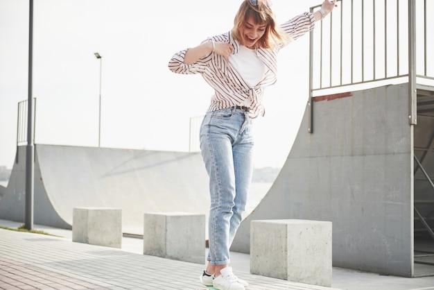 Una giovane donna sportiva che cavalca in un parco su uno skateboard. Foto Gratuite