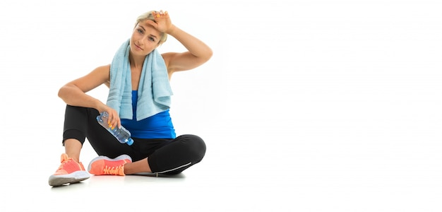 A young sports woman with blonde hair in a black sports axe, black leggings and bright sneakers with a towel around her neck and a bottle of water tired after training. Premium Photo