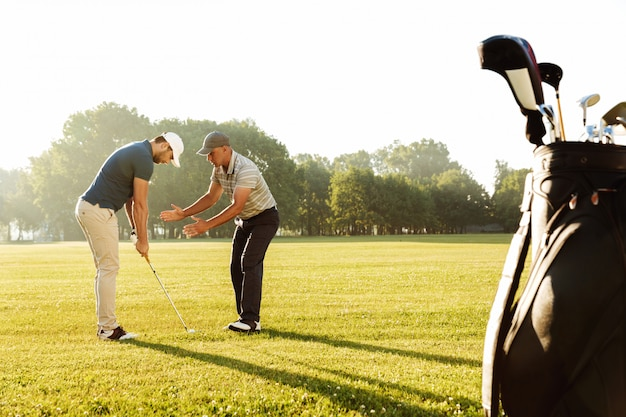 Young sportsman practicing golf with his teacher Free Photo