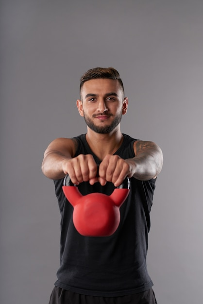 Young sportsman training with kettlebell Free Photo