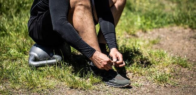 スポーツシューズの靴ひもを結ぶ若いスポーツマン Premium写真