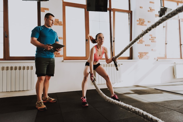 Young sportswoman is exercises in gym with trainer Premium Photo