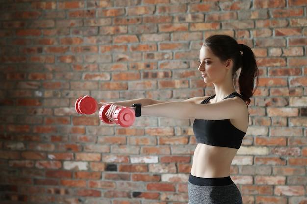 Giovane sportiva con manubri Foto Gratuite